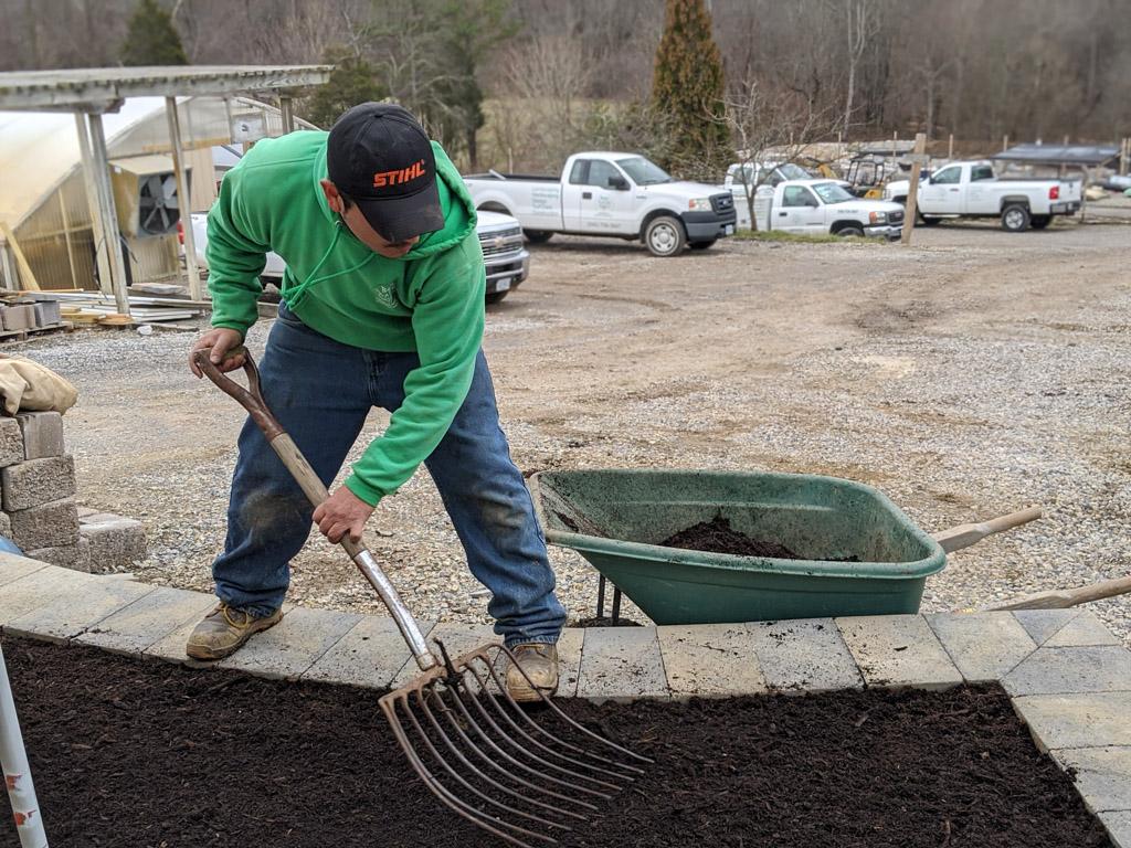 A Back to Nature employee mulching